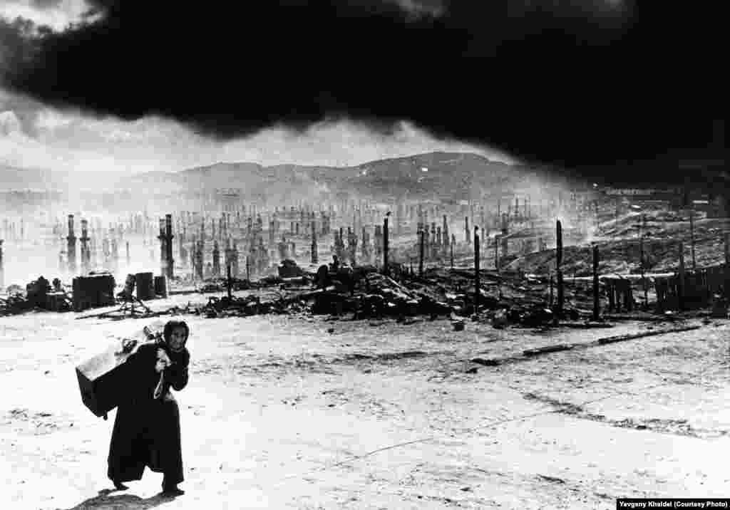 A woman flees Murmansk, in northern Russia, as the city is devastated following Hitler's order to burn it to the ground in late June 1942