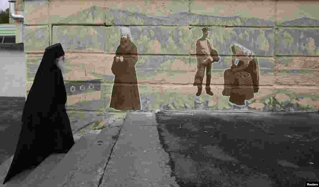 Orthodox monk Father Ioakim, 74, looks at a street graffiti, which displays Siberian characters of the 19th century including an Russian Orthodox monk, in Divnogorsk town outside the Siberian city of Krasnoyarsk. (Reuters/Ilya Naymushin)