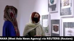 Коронавирустан қатты зардап шеккен Иранда әйел адам маска тақырыбындағы картиналарды тамашалап тұр. Тегеран, Иран. 18 шілде, 2020 жыл.