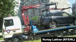Автомобиль эвакуируют с территории, прилегающей к детскому саду. В результате наезда погиб один ребенок, несколько госпитализированы с травмами. Алматы, 20 мая 2015 года.