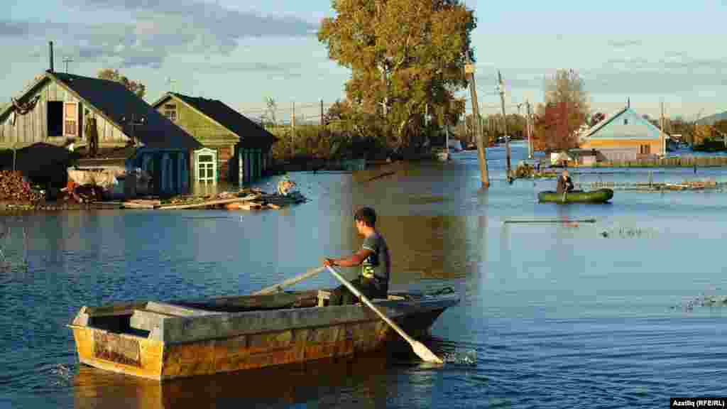 A  man paddles down the flooded streets of a Komsomolsk neighborhood.