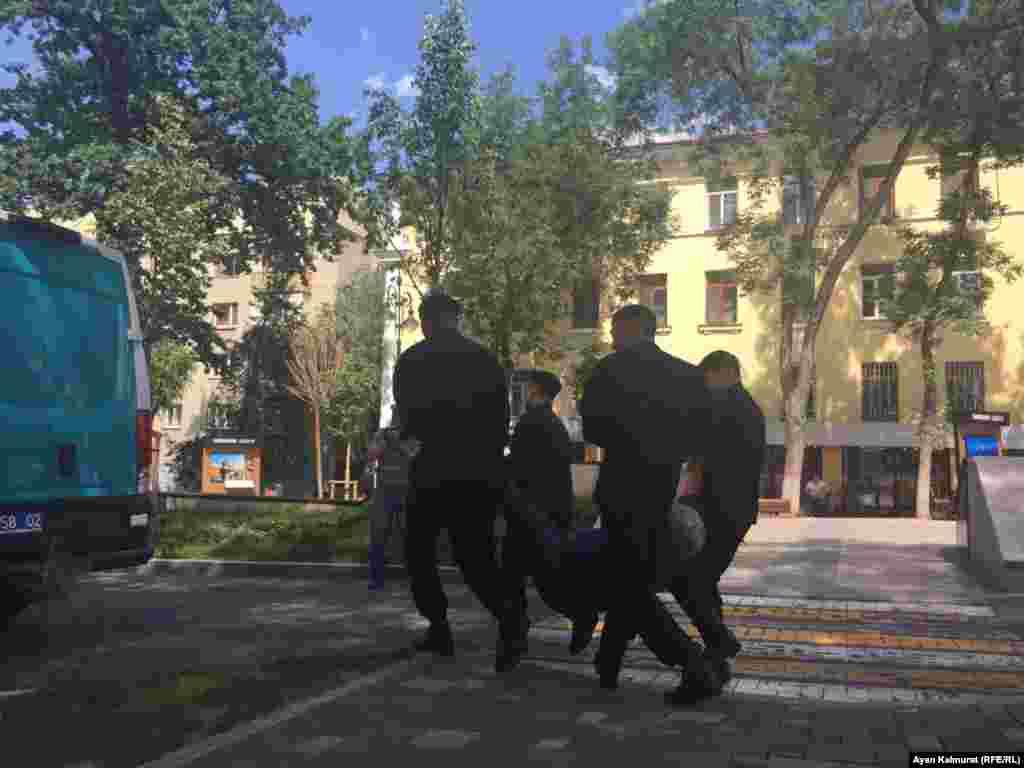 Абай атындагы опера жана балет театрынын жанынан кармалган адамды полиция көтөрүп бара жатат.