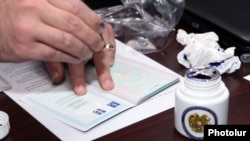 Armenia - A member of the Central Election Commission puts a sample passport stamp designed to prevent multiple voting in elections, Yerevan, 12Feb2013.