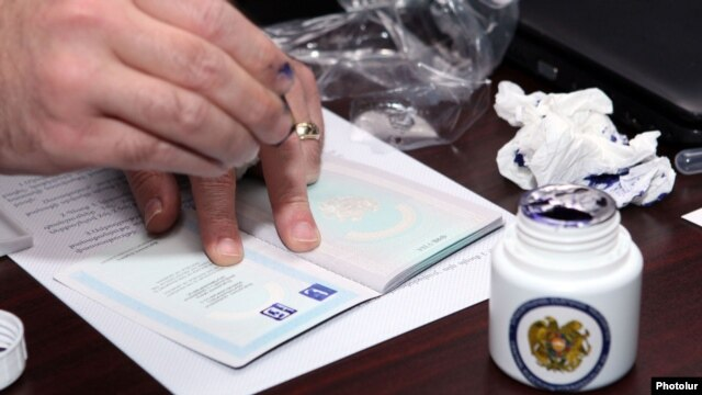 An Armenian election official applies a sample passport stamp designed to prevent multiple voting in elections. Some expatriates fear their identities will be used to commit election fraud.