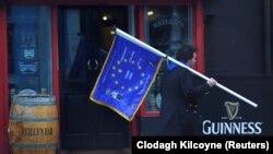 Мужчина с флагом ЕС проходит рядом с пабом в Дублине, столице Ирландии. 4 декабря 2017 года.