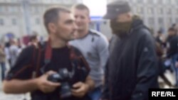 Супрацоўнікі ў цывільным, адзін — з завязаным тварам — перашкаджаюць фотакарэспандэнту Reuters Васілю Фядосенку.