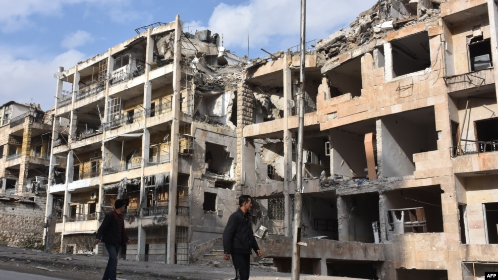 Syrians walk past destroyed buildings in the former rebel-held Ansari district in the northern Syrian city of Aleppo on December 23, after Syrian government forces retook control of the whole city.
