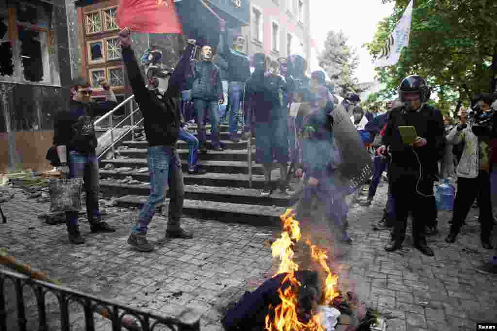 Pro-Russia activists burn uniforms outside the regional prosecutor's office in Donetsk on May 1. (Reuters/Marko Djurica)