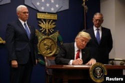 U.S. President Donald Trump signs the executive order titled Protecting The Nation From Foreign Terrorist Entry Into The United States on January 27.