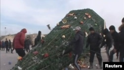 Protesters kick a fallen holiday tree in Zhanaozen on December 16.