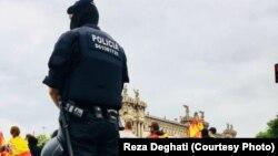 Полицейский наблюдает за участниками акции в день проведения референдума в Каталонии. Барселона, 1 октября 2017 года.
