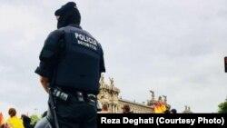 Полицейский наблюдает за участниками акции в день проведения референдума в Каталонии. Барселона, 1 октября 2017 года
