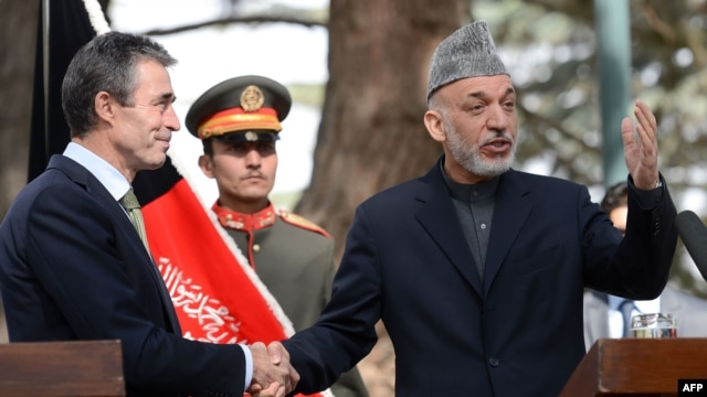 Afghan Preisdent Hamid Karzai (right) gestures as he shakes hands with NATO Secretary-General Anders Fogh Rasmussen in Kabul in mid-October.
