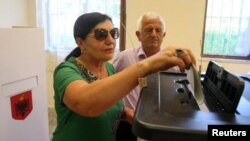 A woman casts her vote during parliamentary elections in Surel, near Tirana, on June 25.
