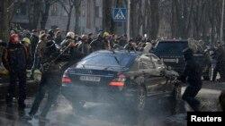 """Представители радикальной оппозиции атакауют машину, выехавшую из здания офиса """"Партии регионов"""""""