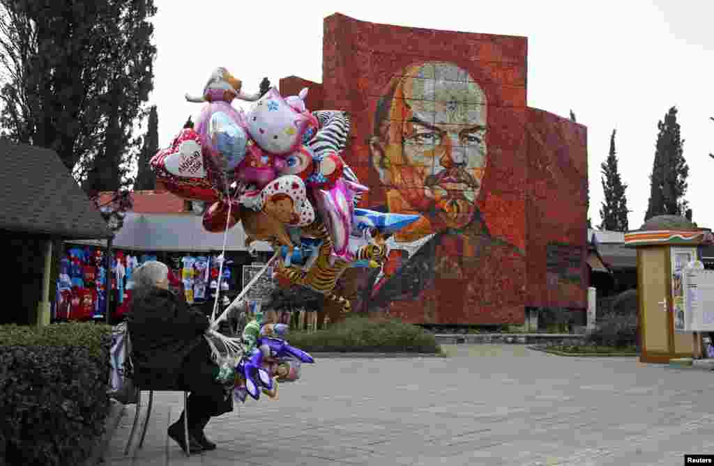 A woman sells balloons in front of a portrait of Soviet founder Vladimir Lenin in Sochi.