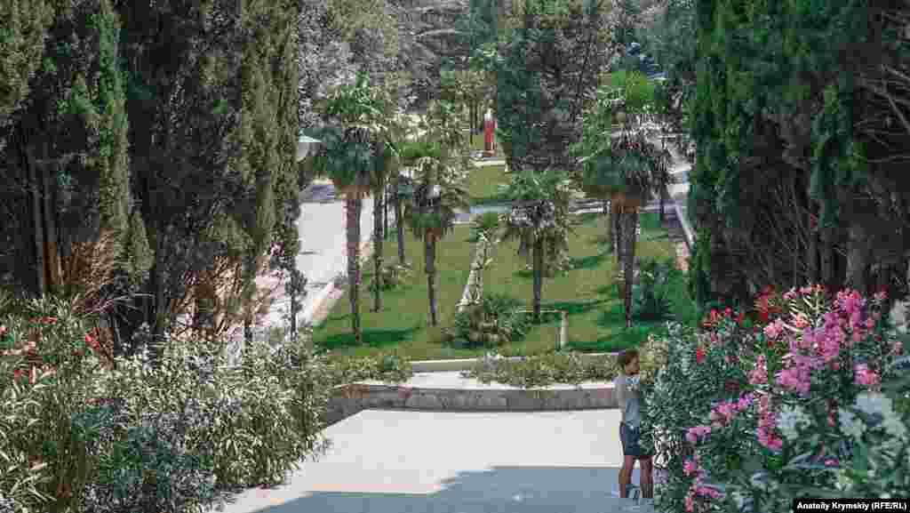 Штатный садовник парка ухаживает за цветами