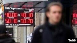 Мужчина проходит рядом с электронным табло с курсами обмена валют. Москва, 6 октября 2014 года.