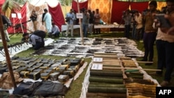 Pakistani policemen stand beside seized weapons displayed for the media in Karachi last month.
