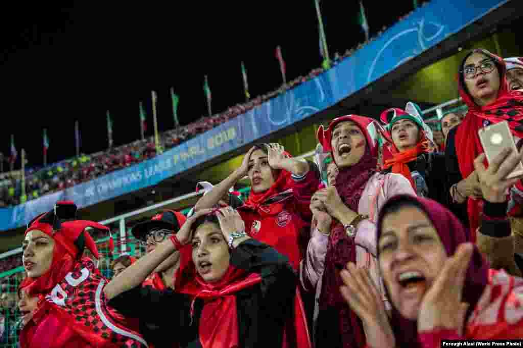 Women follow the Asian Champions League soccer match between Iranian club Persepolis and Japan's Kashima Antlers in Tehran on November 10, 2018. They are watching from a segregated section at the stadium where women must sit. Sports: First Prize, Stories - Forough Alaei