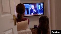 Члени британської родини дивляться виступ прем'єра Бориса Джонсона по телевізору щодо боротьби з коронавірусом. 10 травня 2020 року