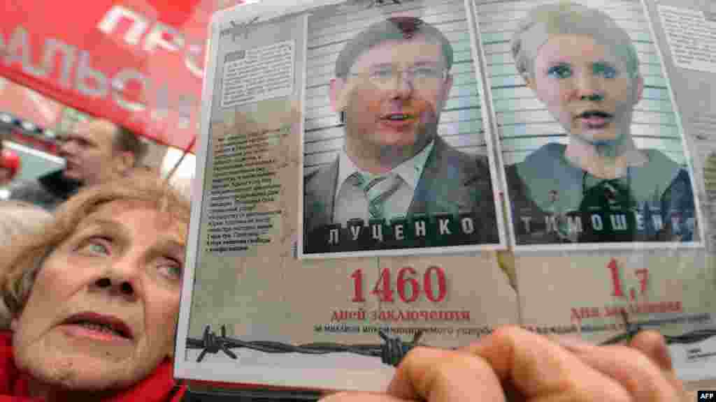 A woman holds a placard with pictures of jailed ex-premier Yulia Tymoshenko and jailed opposition leader Yuriy Lutsenko.