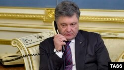 Ukrainian President Petro Poroshenko talks to Nadia Savchenko by phone at the presidential office in Kyiv on April 19.