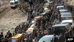 Mourners carry the coffins of the Kurdish victims of a Turkish air raid in its Sirnak province on December 30.