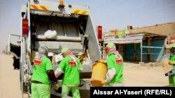 عمال اتراك يزيلون النفايات من شوارع النجف