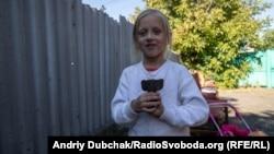 Тома с хвостовиком от мины на соседском дворе, где были ранены ее сестра и двоюродный брат. Марьинка, 24 сентября 2019 года.