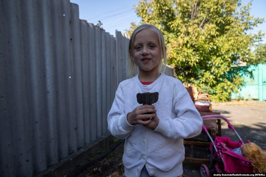 Тома держит осколок снаряда в соседском дворе, где были ранены ее брат и сестра