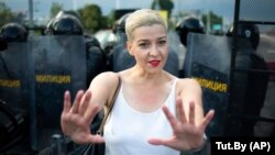 Maryya Kalesnikava, one of opposition presidential candidate Svyatlana Tsikhanouskaya's top aides, gestures in front of riot police during the rally in Minsk on August 30.