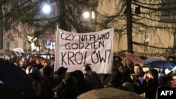 "Poles protested the Kaczynskis' burial at Wawel Castle demonstrate in Krakow on April 13, holding a banner that asks, ""Is he worthy of a king's burial?"""