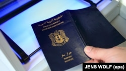 Një pasaport siriane kontrollohet në një qendër për azil-kërkuesit në Gjermani