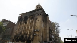 Christians look at a church that was set on fire during clashes between Muslims and Christians in the heavily populated area of Imbaba in Cairo on May 8.