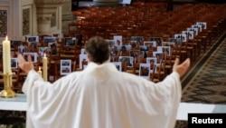 Настоятель храма в Бетюне, департамент Па-де-Кале, проводит пасхальную службу перед фотографиями своих прихожан. 12 апреля 2020