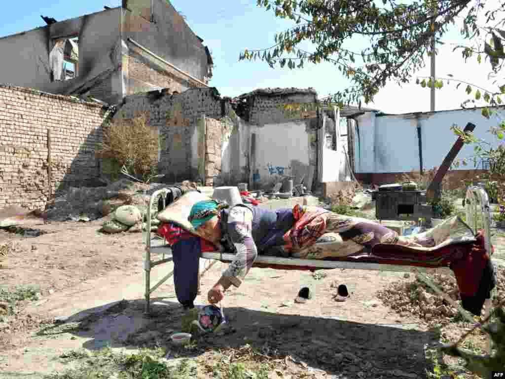 Оштағы өртенген үйінің орнында жатқан өзбек әйелі. 20 маусым 2010 жыл.
