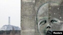 Ýüzün surat çekilen diwaryň arkasynda Çernobyl atom elektrik stansiýasyndaky 4-nji reaktoryň üstüni örtýän sarkofag görünýär, 4-nji aprel.