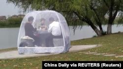Njerëzit shijojnë ushqimin brenda një tende për të parandaluar sëmundjen e koronavirusit të ri (COVID-19) në një park në Nanjing, provinca Jiangsu