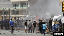 Residents gather at the site of a bomb attack in central Baghdad on July 31 that killed 20 people.