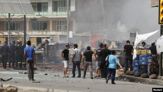 Iraqis gather at the site of a bomb attack in central Baghdad on July 31.