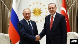 Russian President Vladimir Putin (left) shakes hands with Turkish President Recep Tayyip Erdogan at the Presidential Complex in Ankara on September 28.