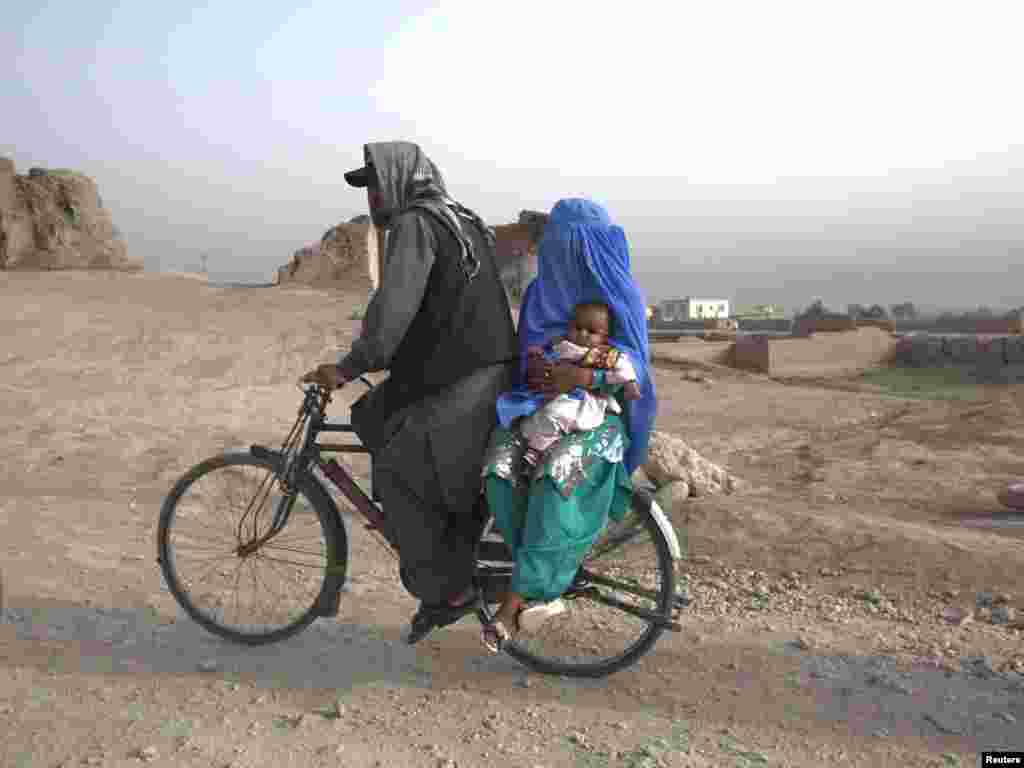 An Afghan family rides a bicycle on a road in Kabul on July 15. Photo by Ahmad Masood for Reuters