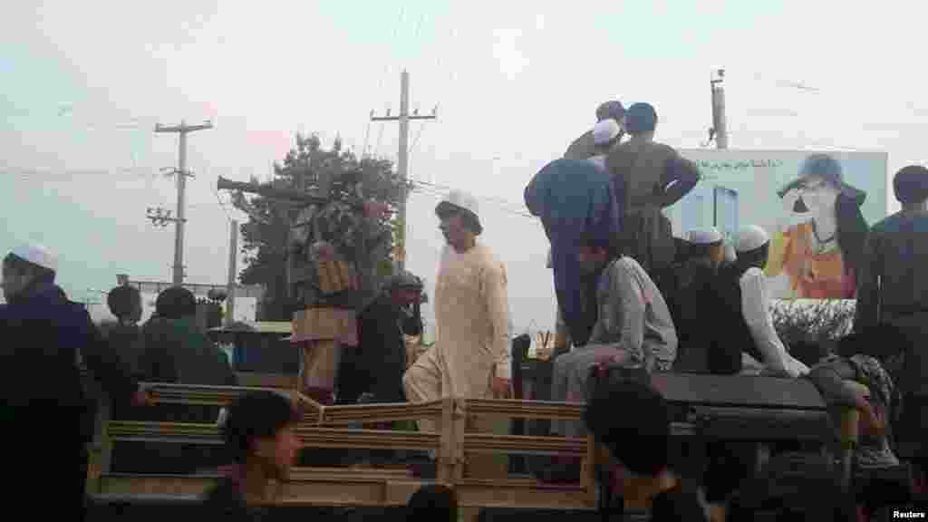 Taliban fighters and residents on top of a military vehicle in Kunduz after it fell to the Taliban.