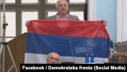Oopposition Democratic Front deputy Jovan Vucurovic takes out a Serbian tricolor flag during a session of the Montenegrin parliament in Podgorica on March 4.