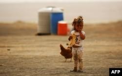 Ребенок ест кусок хлеба в лагере беженцев недалеко от сирийского города Ракка. 11 мая 2017 года.