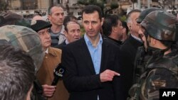 Syrian President Bashar al-Assad (center) speaks to soldiers during a tour of the restive Baba Amr neighborhood of Homs late last month.