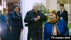 Türkmen prezidenti ejesi we kakasy bilen saýlaw uçastogynda ses berýär, Türkmen TW-sinden alnan surat.