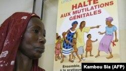 Женщина проходит мимо плаката, поддерживающего отмену женского обрезания