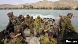 Kazakh troops in an amphibious vehicle while crossing the Ili river during military exercises outside Almaty in August 2010